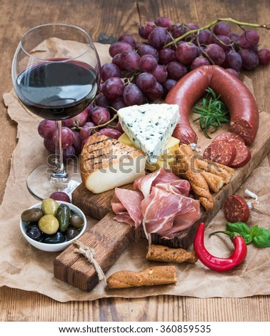 Glass of red wine, cheese and meat board, grapes,fig, strawberries, honey and bread sticks  on rustic wooden table, white background, selective focus - stock photo