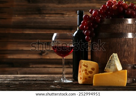 Glass of red wine, cheeses and grapes on brown wooden background - stock photo