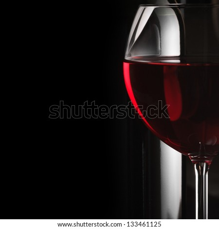 Glass of red wine close-up on dark background with copy space.