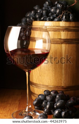 Glass of red wine, dark grape and souvenir barrel on wooden surface.