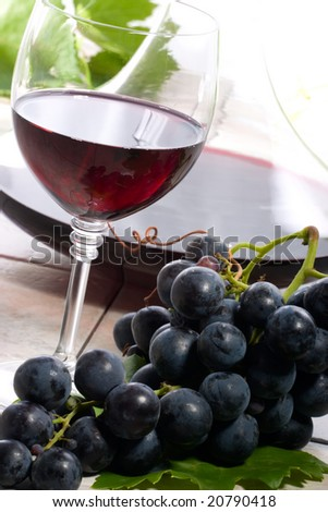 Glass of red wine, decanter and fresh cut black wine grape bunch.