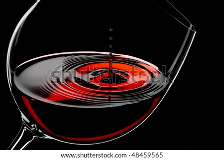 glass of red wine, drops in motion, studio shot - stock photo
