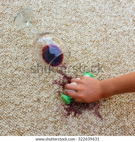 Glass of red wine fell on carpet. Female hand cleans floor with sponge and detergent. - stock photo