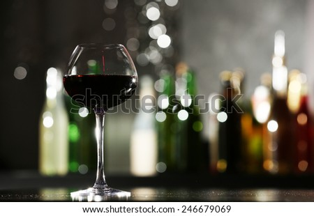 Glass of red wine in bar on blurred background - stock photo
