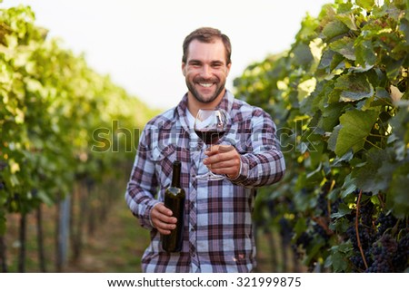 Glass of red wine in hand, the young winemakers in the vineyard - stock photo
