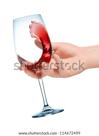 Glass of red wine in hand. Wine tasting. - stock photo