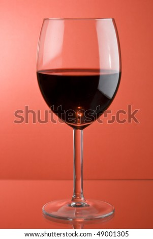 glass of red wine in red background