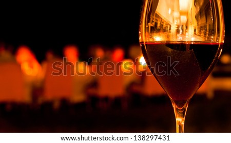 Glass of Red Wine in Romantic Restaurant Setting - stock photo