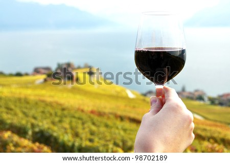 Glass of red wine in the hand against vineyards in Lavaux region, Switzerland - stock photo