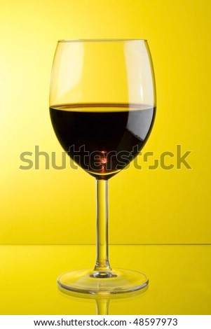 glass of red wine in yellow background