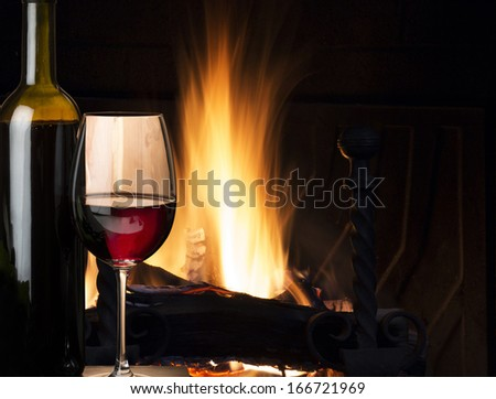 glass of red wine near the fireplace - stock photo