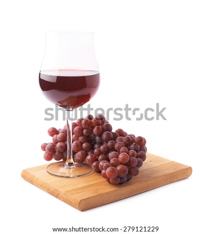 Glass of red wine next to a branch of dark red grapes over the wooden serving board, composition isolated over the white background - stock photo