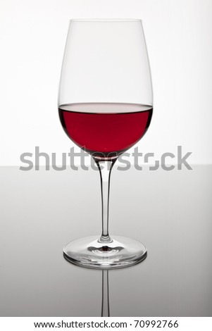 Glass of red wine on a bright background and with soft reflection