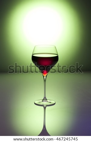 Glass of red wine on a green background / Red wine / Nadale