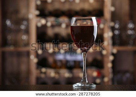 Glass of red wine on bar background - stock photo