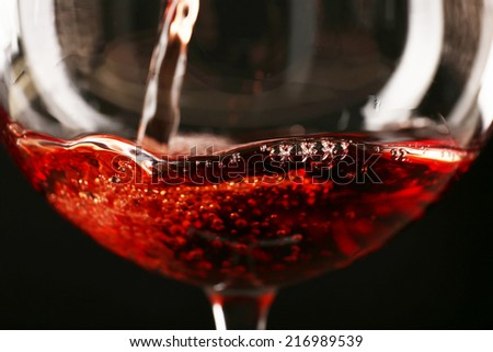 Glass of red wine on dark background closeup - stock photo