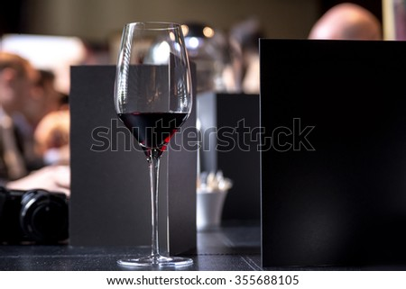Glass of red wine on restaurant table - stock photo