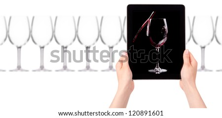 glass of red wine on tablet computer screen isolated on a white background