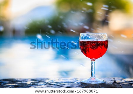 Glass of red wine on the edge of the swimming pool - stock photo