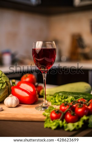 Glass of red wine on the table near fresh salad vegetables at home - close up blurred photo - stock photo