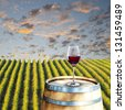 Glass of red wine on wood barrel with vineyard scene in the background - stock photo
