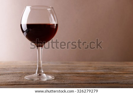 Glass of red wine on wooden table - stock photo