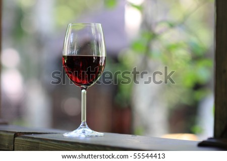 Glass of red wine on wooden windowsill of summer house