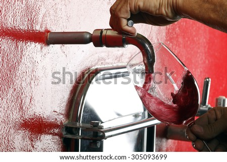 glass of red wine vineyard tap - stock photo