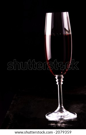 Glass of red wine. White reflections on the wine glass.Low light and black background.