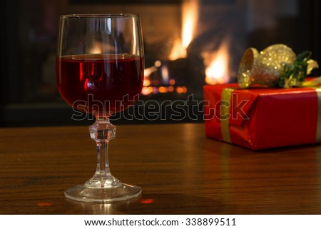 Glass of red wine with a Christmas present and fireplace in background - stock photo