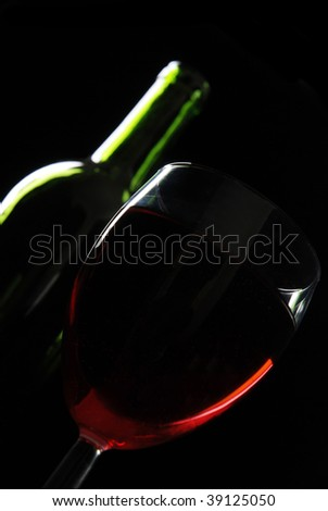 Glass of red wine with a wine bottle behind isolated on black.