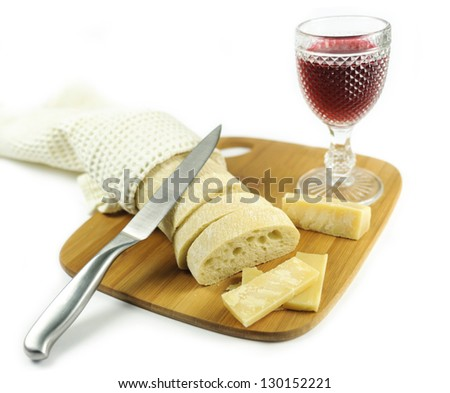Glass of red wine with bread and pieces of cheese on the cutting board with knife - stock photo