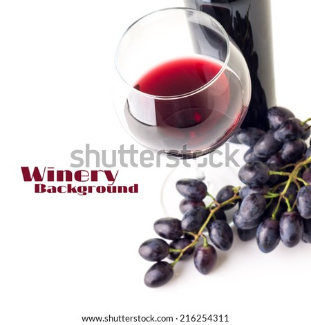Glass of red wine with bunch of grapes  and bottle isolated on white background. Selective focus - stock photo
