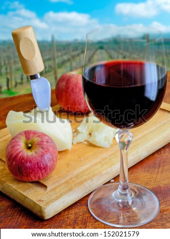 glass of red wine with cheese and apple on a chopping board - stock photo