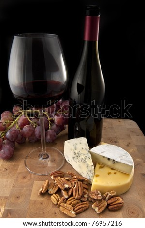 Glass of red wine with food on wooden table