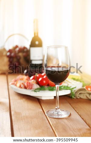 Glass of red wine with food on wooden table closeup