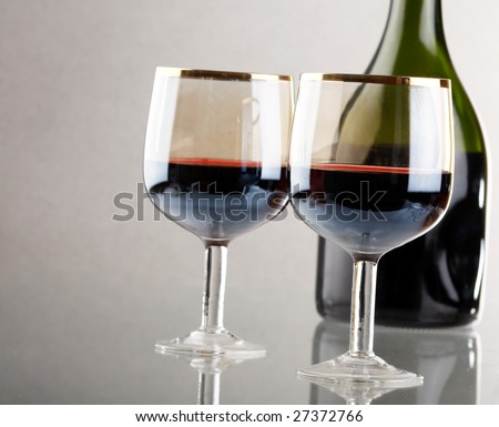 Glass of red wine with glass and bottle