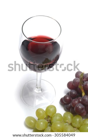 glass of red wine, with grapes - stock photo