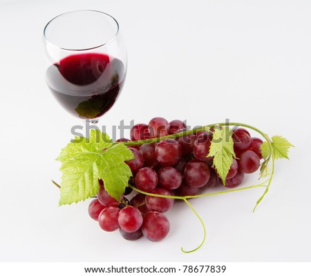 Glass of red wine with grapes, neutral background