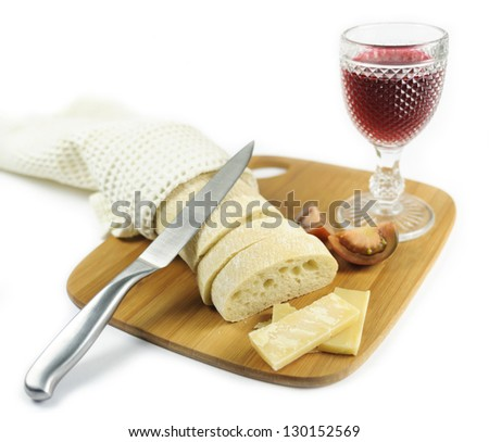 Glass of red wine with pumpkin seeds, tomatoes, bread, pieces of cheese on the cutting board with knife - stock photo