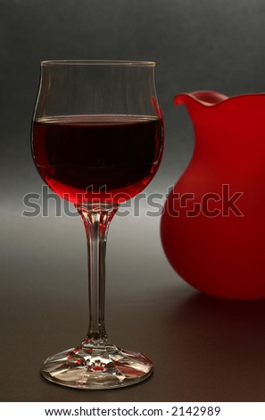 glass of red wine with red vase in the background - stock photo