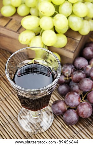 Glass of red wine with some grapes. - stock photo