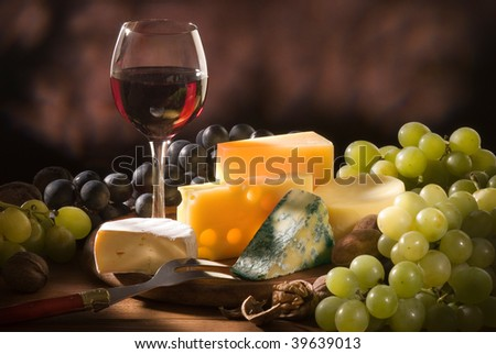 Glass of red wine with various types of cheese and garnishes - stock photo