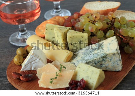 Glass of red wine with various types of cheese, fruits and appetizers