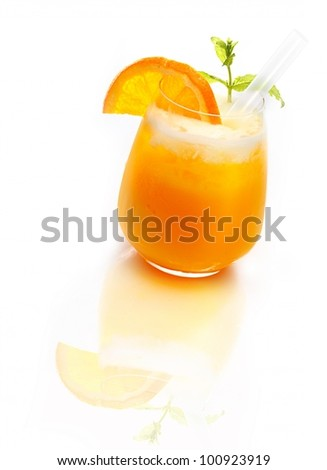 Glass of refreshing orange cocktail topped with ice on a reflective white surface - stock photo