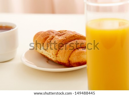 Glass of refreshing orange fruit juice and croissant over business paper - stock photo