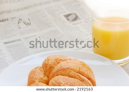 Glass of refreshing orange fruit juice and croissant over business paper with graphs and word 'innovative', macro - stock photo