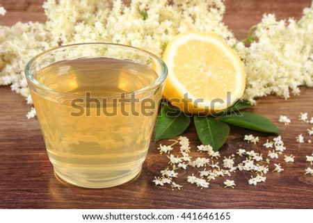 Glass of refreshment healthy juice, elderberry flowers and lemon on rustic board, alternative medicine and therapy - stock photo