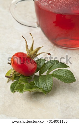 Glass of rose hip tea and a fresh rose hip - stock photo