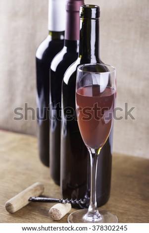 glass of rose wine, corkscrew on the background bottles - stock photo
